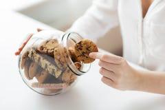 Feche acima das mãos com as cookies do chocolate no frasco Fotos de Stock