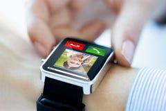 Feche acima das mãos com entrante chamam o smartwatch fotografia de stock royalty free