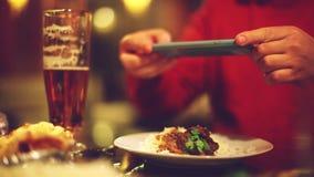 Feche acima das mãos com o smartphone que toma um PIC do alimento para a site de rede social na barra ou no bar 1920x1080 filme