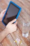 Feche acima das mãos com PC, comprimidos e água da tabuleta Fotografia de Stock Royalty Free