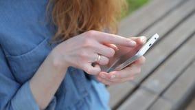 Feche acima das mãos da compra do telefone celular do uso da jovem mulher em linha e pague com Internet banking video estoque