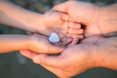 Feche acima das mãos da criança e do homem com coração imagem de stock