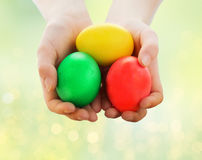 Feche acima das mãos da criança que guardam ovos da páscoa Imagens de Stock Royalty Free