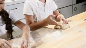 Feche acima das mãos da criança que jogam com a massa que rola o O menino do cozinheiro chefe e a menina do cozinheiro chefe cozi video estoque