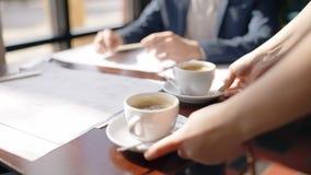 Feche acima das mãos da empregada de mesa que põem duas xícaras de café à tabela na frente do arquiteto que trabalha sobre o mode video estoque