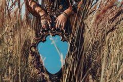 Feche acima das mãos da jovem mulher que guardam o espelho fora Foto de Stock