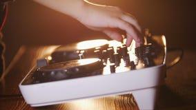 Feche acima das mãos da música dos jogos do DJ que mistura e que risca no equipamento da música da plataforma giratória Equipamen video estoque