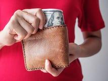 Feche acima das mãos da mulher com carteira e dinheiro do dólar Fotos de Stock