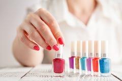 Feche acima das mãos da mulher com os vernizes para as unhas de cores diferentes Fotografia de Stock