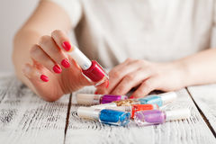 Feche acima das mãos da mulher com os vernizes para as unhas de cores diferentes Fotos de Stock Royalty Free