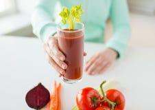 Feche acima das mãos da mulher com suco e vegetais Imagem de Stock