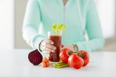 Feche acima das mãos da mulher com suco e vegetais Foto de Stock