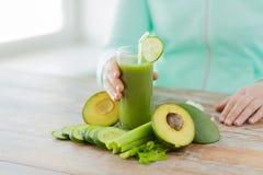 Feche acima das mãos da mulher com suco e vegetais Fotos de Stock Royalty Free