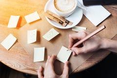 Feche acima das mãos da mulher que escrevem etiquetas das notas dos differents pelo lápis de madeira Mulher bonita nova que tira  Fotos de Stock