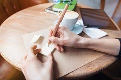 Feche acima das mãos da mulher que escrevem stickies das notas do amor pelo lápis de madeira Mensagem bonita nova do amor do dese Foto de Stock