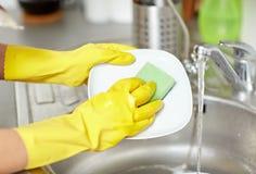 Feche acima das mãos da mulher que lavam pratos na cozinha imagens de stock