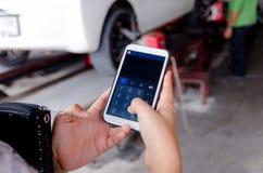 Feche acima das mãos da mulher que usa a calculadora esperta móvel appl do telefone Foto de Stock Royalty Free