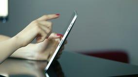 Feche acima das mãos da mulher usando o tablet pc interno video estoque
