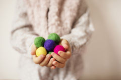 Feche acima das mãos das crianças que guardam bolas coloridas de feltro Criança, palmas da criança Uma menina mantém-se nos punha imagem de stock royalty free