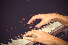 Feche acima das mãos das moças, jogando o piano filte do tom do vintage Fotografia de Stock Royalty Free