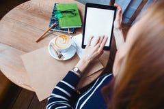 Feche acima das mãos das mulheres que guardam a tabuleta digital com a tela vazia para seu texto da propaganda, leitura fêmea do  Imagens de Stock Royalty Free