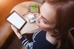 Feche acima das mãos das mulheres que guardam a tabuleta digital com a tela vazia para seu texto da propaganda, leitura fêmea do  Foto de Stock Royalty Free