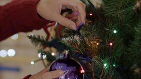 Feche acima das mãos das mulheres que penduram o brinquedo do vintage na árvore de Natal vídeos de arquivo