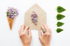 Feche acima das mãos das mulheres que tocam no envelope aberto do papel do ofício enchido com as flores lilás roxas cercadas por  Imagem de Stock