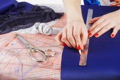 Feche acima das mãos de um desenhador de moda no trabalho com tela de pano Mãos fêmeas no trabalho com a régua para o pano novo C Fotografia de Stock