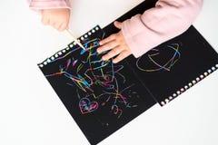 Feche acima das mãos de um desenho da criança pequena no papel de pintura do risco mágico com vara do desenho imagens de stock