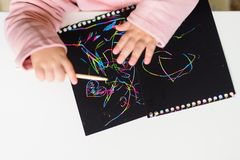 Feche acima das mãos de um desenho da criança pequena no papel de pintura do risco mágico com vara do desenho fotografia de stock