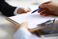 Feche acima das mãos de um executivo que guardam uma pena e que indicam onde assinar um contrato no escritório Foto de Stock