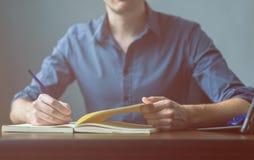 Feche acima das mãos de um homem de negócios em uma camisa azul que assina ou que redige um original em uma folha do caderno imagem de stock