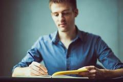 Feche acima das mãos de um homem de negócios em uma camisa azul que assina ou que redige um original em uma folha do caderno fotografia de stock