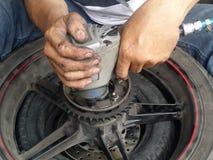 Feche acima das mãos de um mecânico da motocicleta usando uma arma pneumática Fotografia de Stock Royalty Free