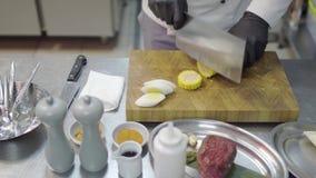 Feche acima das mãos de um shuf não reconhecido profissional em luvas pretas estão desbastando o milho em partes redondas na cozi video estoque