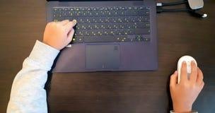 Feche acima das mãos de uma estudante usando o rato e o teclado Criança da mão que joga o computador na vista superior, conceito  imagens de stock royalty free