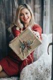 Feche acima das mãos de uma menina para abrir seu presente em uma caixa fotografia de stock