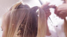Feche acima - das mãos do cabeleireiro que fazem a divisão do cabelo para uma mulher em um salão de beleza filme
