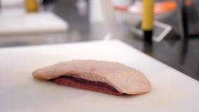Feche acima das mãos do cozinheiro com uma faca que corta a carne do peito de pato filme