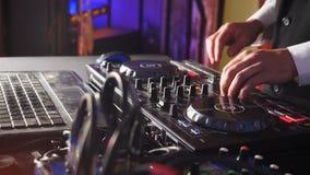 Feche acima das mãos do DJ que jogam a música, misturando Controlador Desk do misturador do DJ no partido de disco do clube notur filme