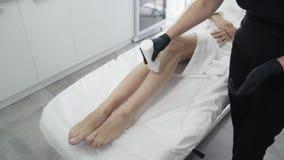 Feche acima das mãos do doutor nas luvas põe o gel sobre o pé do paciente antes do procedimento de remoção do cabelo do laser, mo video estoque