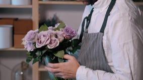 Feche acima das mãos do florista homem que faz o grupo no florista povos, negócio, venda e conceito floristry Ramalhete com video estoque