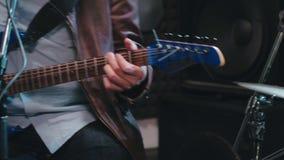 Feche acima das mãos do guitarrista e do baterista que jogam a música video estoque