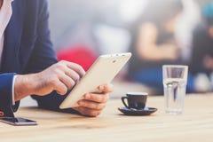 Feche acima das mãos do homem de negócios que guardam o dispositivo digital da tabuleta no café Espaço para a cópia foto de stock