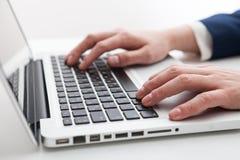 Feche acima das mãos do homem de negócios usando o laptop Foto de Stock Royalty Free