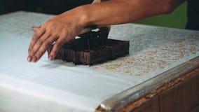 Feche acima das mãos do homem que aplicam a cera para fazer o batik vídeos de arquivo