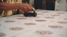 Feche acima das mãos do homem que aplicam a cera para fazer o batik filme