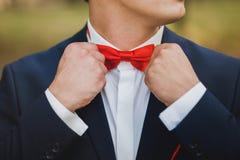 Feche acima das mãos do homem que corrigem o bowtie vermelho O homem veste s azul Foto de Stock Royalty Free
