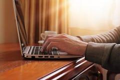 Feche acima das mãos do homem que trabalham no portátil no interior clássico luxuoso do estilo Imagem de Stock